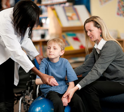 Special needs boy with doctor and mother.
