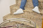 Cropped image of a man leg in wheelchair falling downstairs